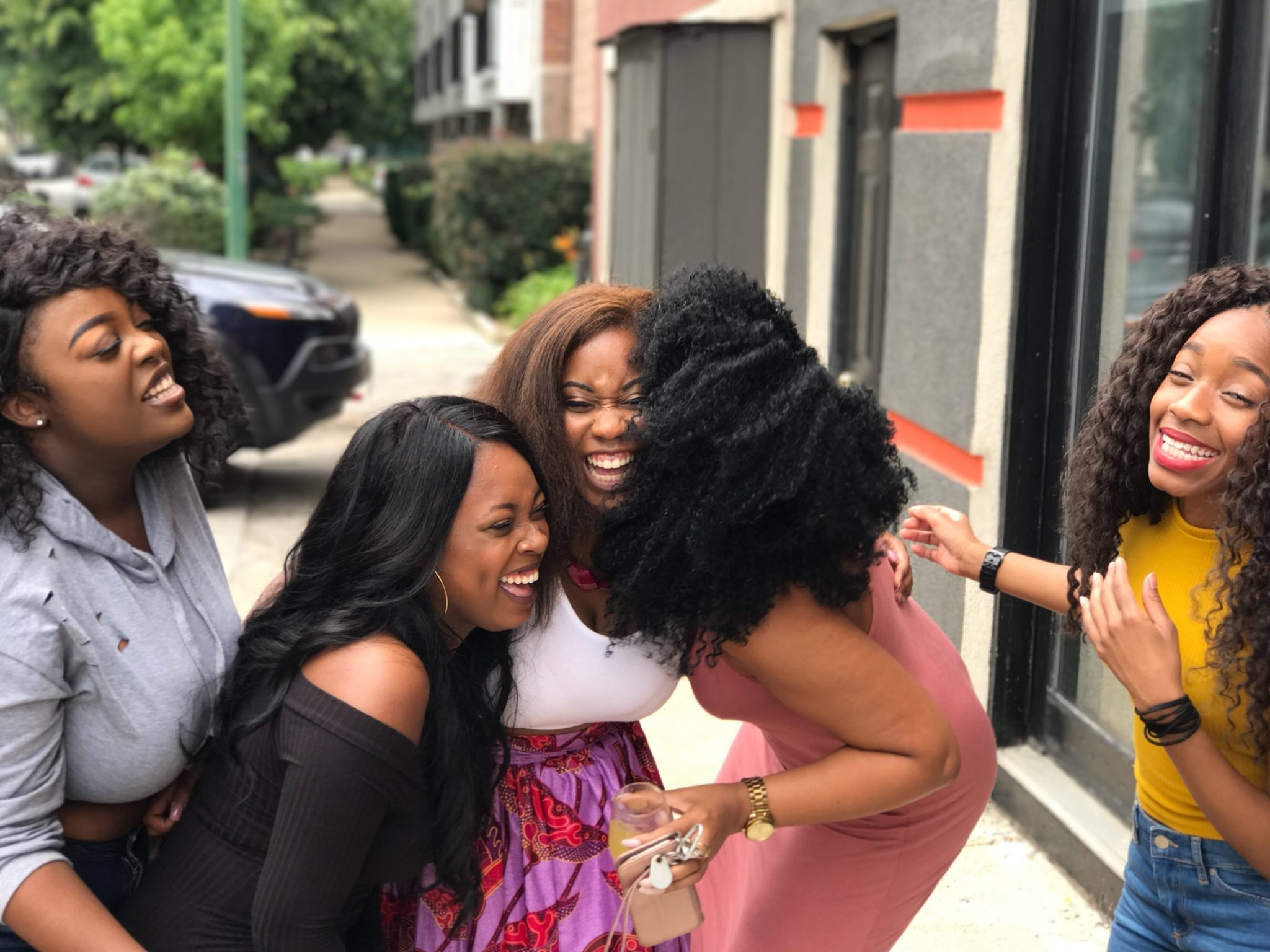 Group of five women, laughing together on a sidewalk.