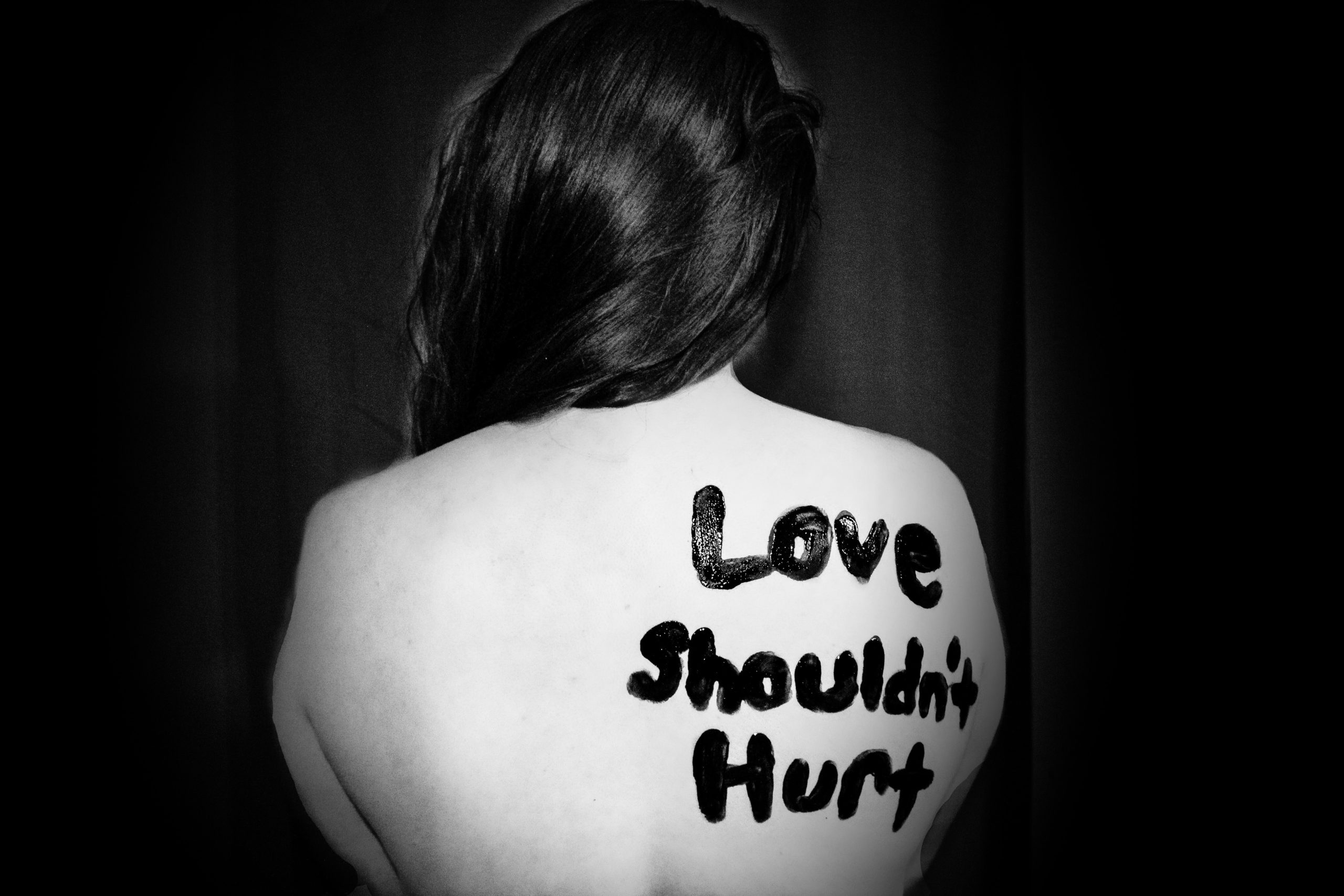 "A black and white photo of a woman's back, with ""Love shouldn't hurt"" painted on her right shoulder blade."