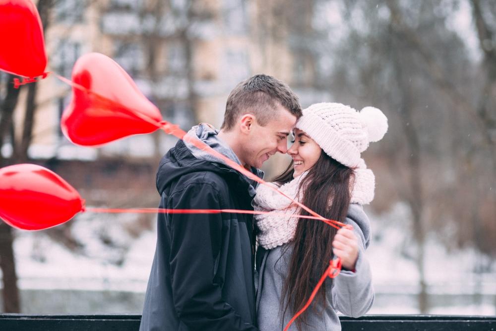 Couple holding heart-shaped balloons.