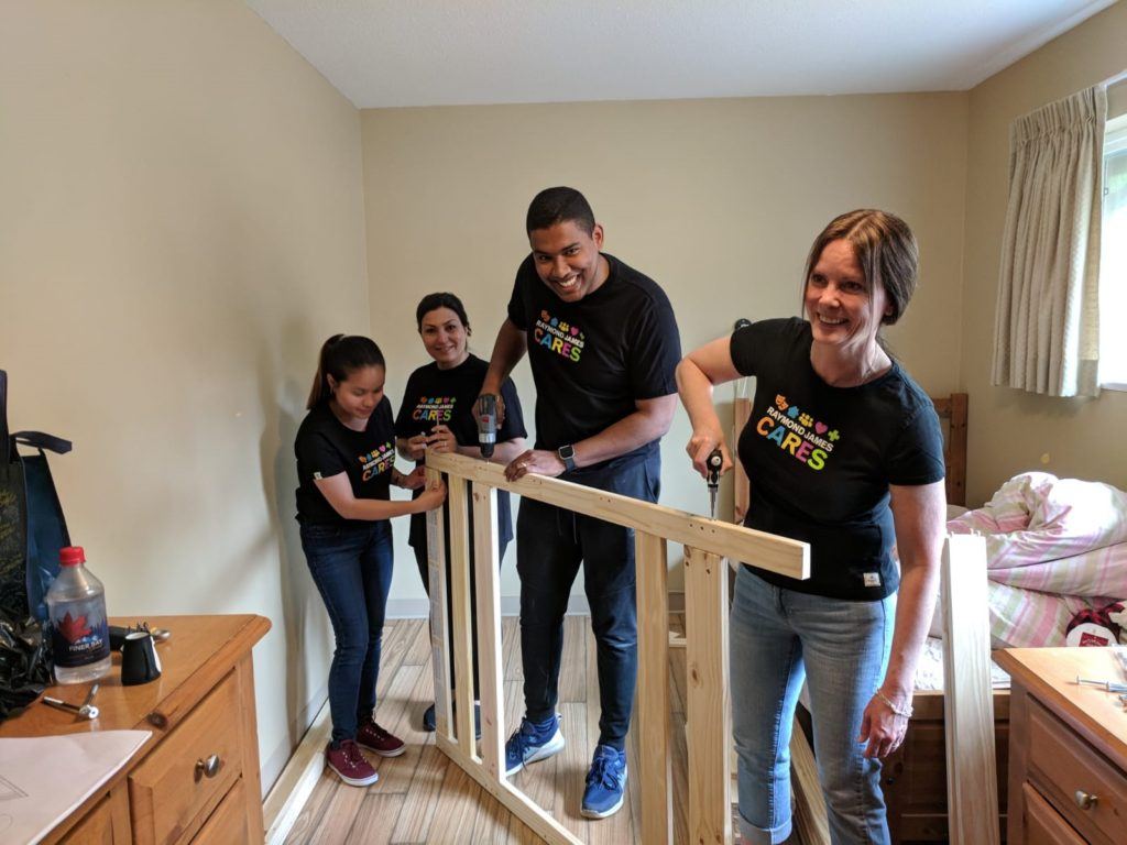 Raymond James Canada Foundation volunteers help assemble a bed at the Dixon Transition Society