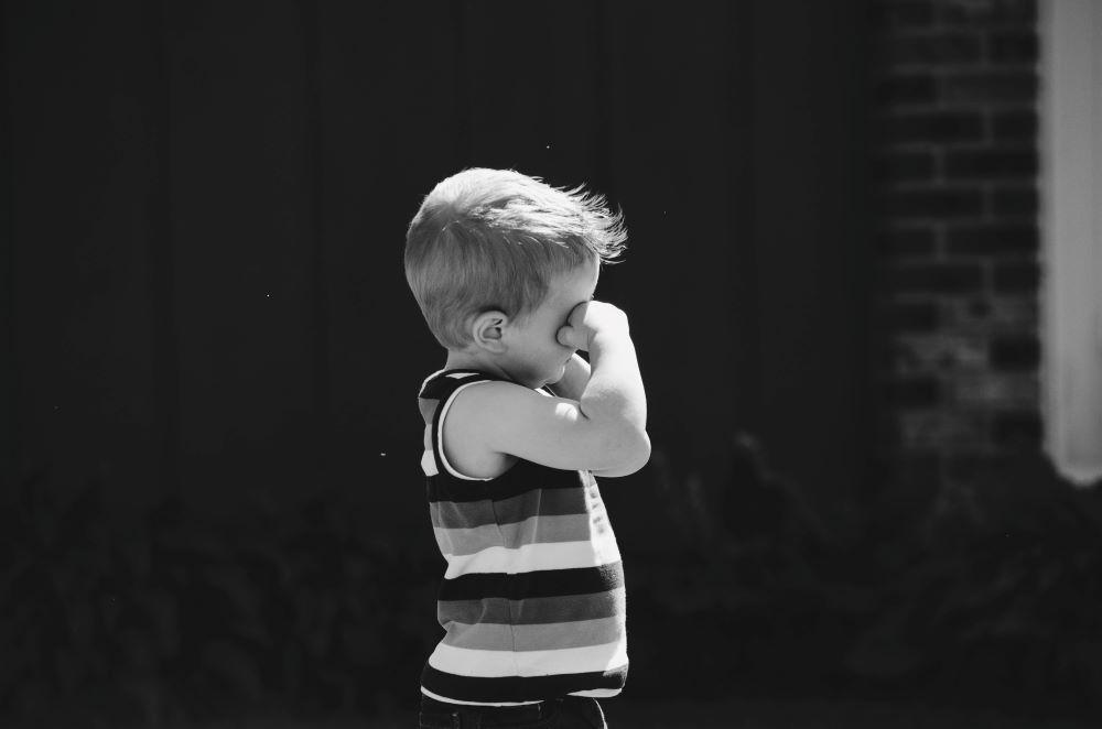 Sad boy wipes eye.