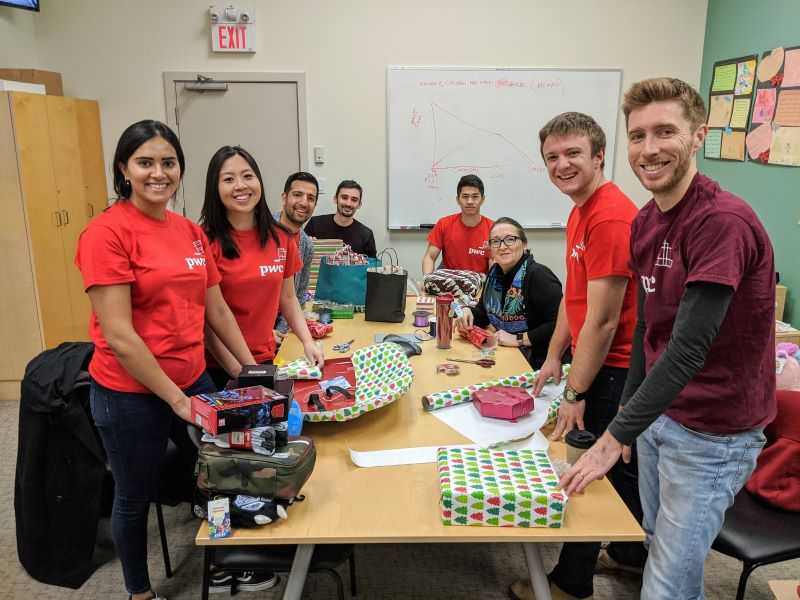 A group of male and female volunteers at the Dixon Society help wrap gifts