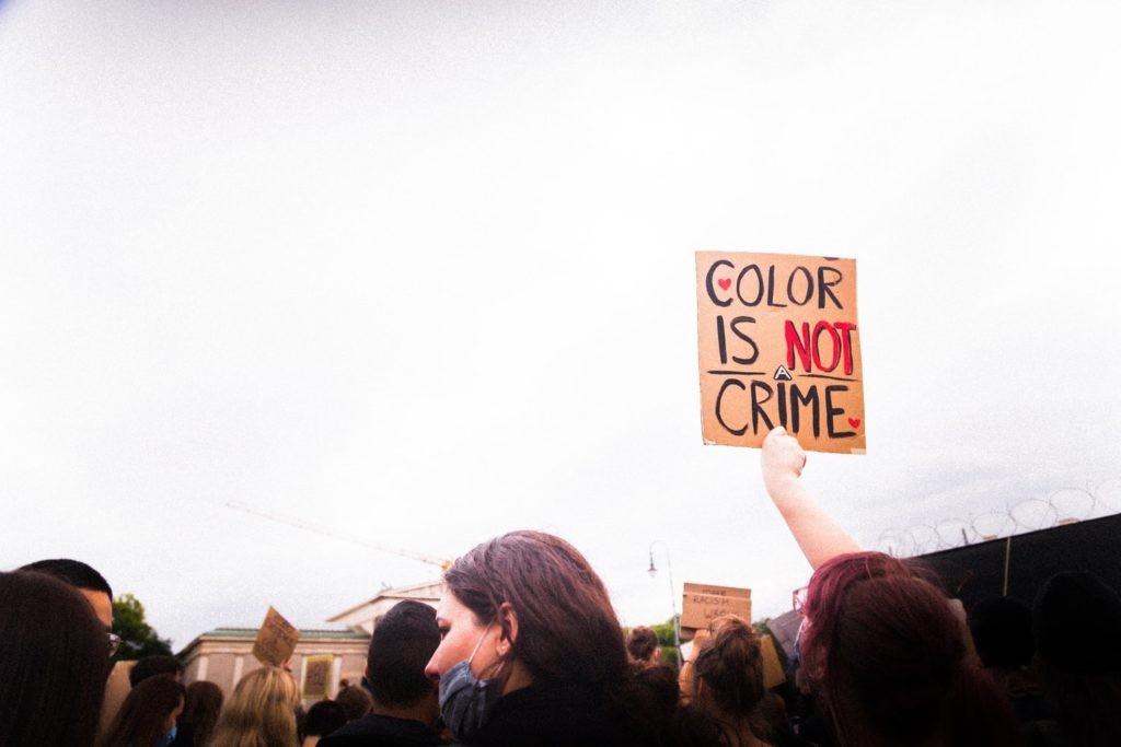 """A group of protestors. One is holding up a sign reading """"color is not a crime"""""""